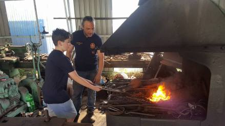 Darren Block instructing a young boy who wants to be a blacksmith